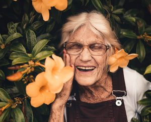 Photo of an old laughing woman amidst orange flowers